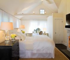 small bedroom with fireplace and twin ivory bedroom table lamps