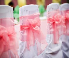 enchanting white folding chair covers with pink ribbon