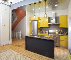 modern small kitchen with metal island and yellow cabinets