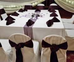 white folding chair covers with old purple ribbons