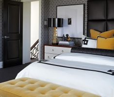 comfortable modern black and white bedroom with tufted yellow ottoman bedroom